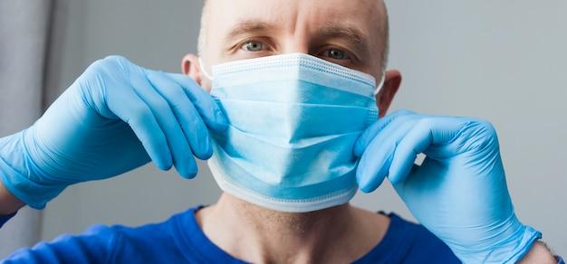 Seguro médico cirujano joven en guantes de látex con máscara médica en la cara