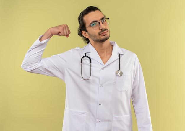 Seguro médico varón joven con gafas ópticas vistiendo túnica blanca con estetoscopio haciendo gesto fuerte