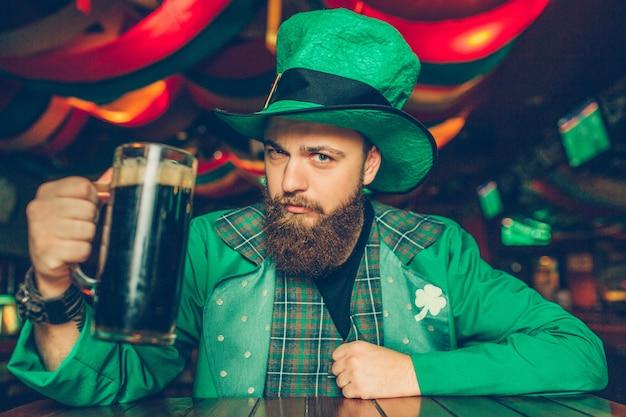 Seguro y serio joven en traje verde de san patricio sentarse a la mesa en el pub y posar. sostiene una jarra de cerveza oscura.