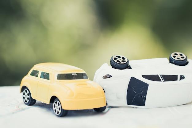Seguro de vehículo concepto de accidente de auto: dos accidentes de autos en miniatura se estrellan en la carretera, juguetes rotos