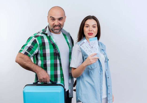 Seguro de viaje adulto pareja hombre sosteniendo maleta y mujer sosteniendo boletos de viaje ambos mirando