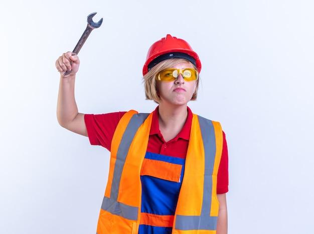 Seguros de mujer joven constructor en uniforme con gafas levantando una llave de boca aislada sobre fondo blanco.