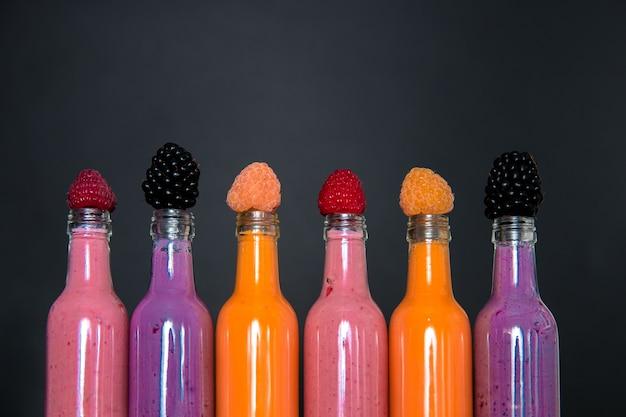 Seis botellas con batidos y frambuesa