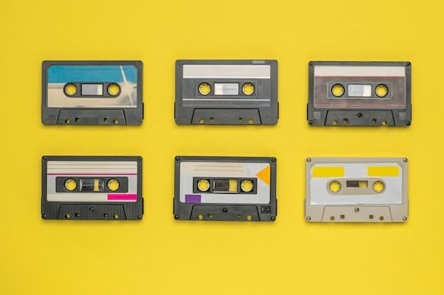 Seis casetes de audio con cinta magnética sobre una superficie amarilla