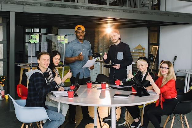 Seis creativos jóvenes empresarios multirracionales y arquitectos que trabajan en la oficina