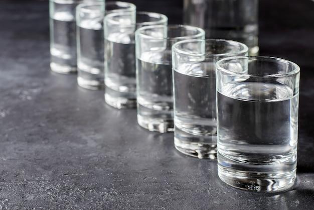 Seis disparos de vodka en una fila. copia espacio