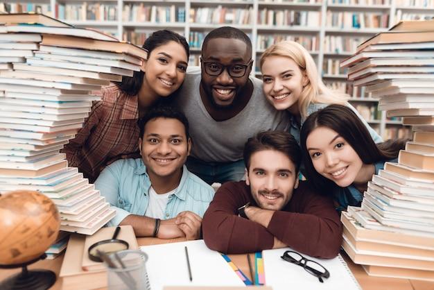 Seis estudiantes étnicos de raza mixta en la biblioteca.