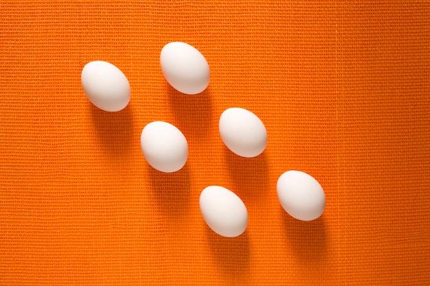 Seis huevos de gallina blanca sobre una naranja