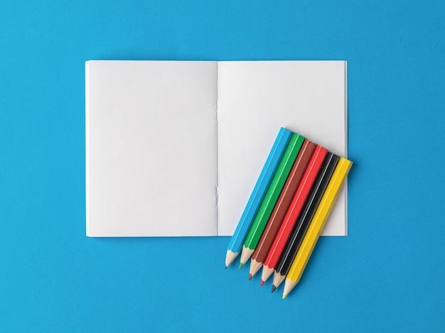 Seis lápices de colores en un cuaderno abierto sobre un fondo azul. papelería y útiles escolares.