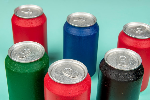 Seis latas frías de refresco de diferentes colores.