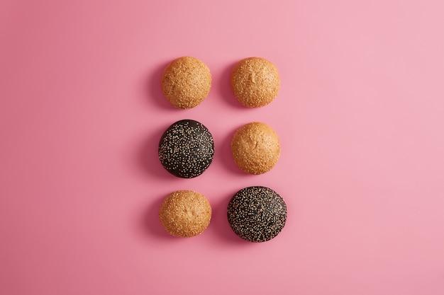 Seis pequeños bollos de hamburguesa suaves al horno espolvoreados con sésamo. hacer hamburguesa o sándwich. fondo rosa, plano laical. dos bollos negros de tinta de sepia. concepto de comida rápida. productos de panadería