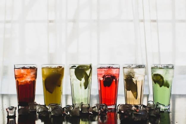 Seis vasos de cócteles de frutas rodeados de cubitos de hielo.