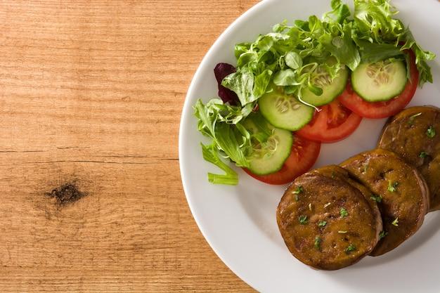 Seitán con verduras en la mesa de madera vista superior de carne falsa copia espacio