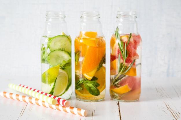 Selección de agua infundida en botellas de vidrio, fondo de madera rústica