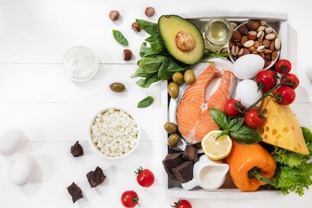 Selección de alimentos cetogénicos bajos en carbohidratos en blanco, vista superior