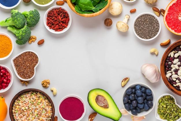 Selección de alimentos limpios y saludables: frutas, verduras, semillas, superalimentos, nueces, bayas