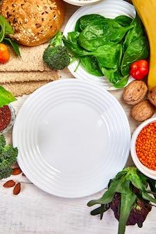 Selección de alimentos ricos en fibra sobre fondo blanco de madera alrededor de un plato vacío