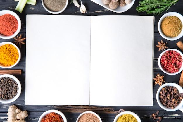 Selección colorida de hierbas y especias con libro de recetas blanco en blanco. ingredientes aromáticos en mesa de madera.