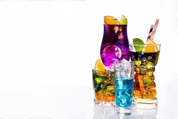 Selección de coloridas bebidas festivas, bebidas alcohólicas y cócteles en elegantes copas en blanco