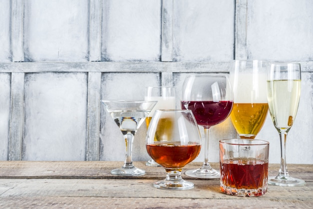Selección de diferentes bebidas alcohólicas: cerveza, vino tinto, champán, coñac, whisky en varias copas.