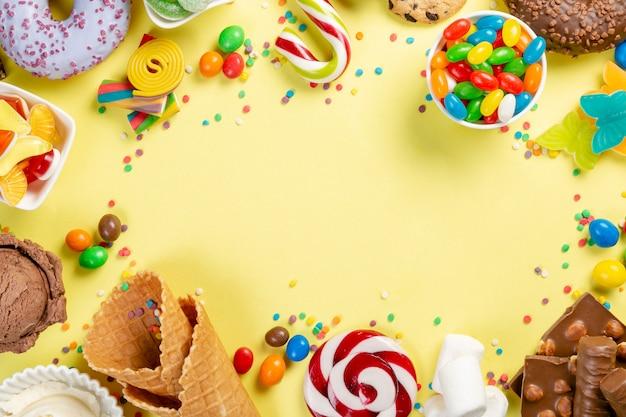Selección de dulces de colores: chocolate, rosquillas, galletas, paletas, helado.