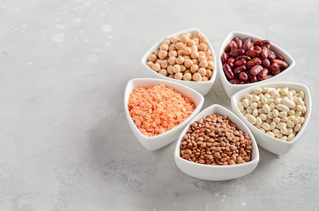 Selección de legumbres secas, lentejas y guisantes en cuencos blancos sobre hormigón gris
