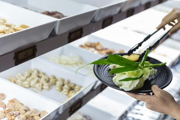 Selección manual y pellizco de verduras frescas en plato negro.