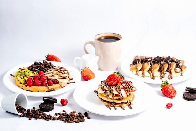 Selección de panqueques de frutas con chocolate caliente