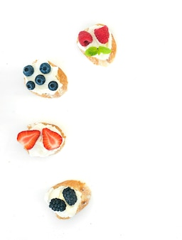 Selección de pequeños bocadillos dulces con queso crema y bayas frescas del bosque.