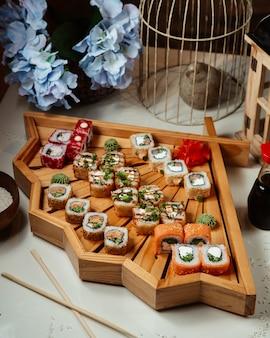 Selección de rollos de sushi en una bandeja decorativa de madera.