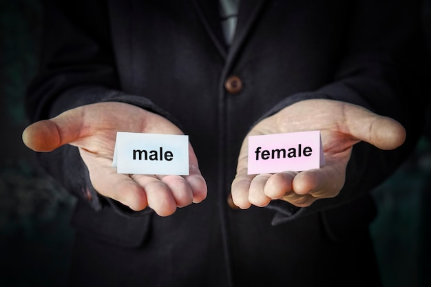 Selección de sexo al nacer. cambio de sexo. elección de orientación sexual. concepto. tabletas con inscripciones masculinas y femeninas en diferentes manos.