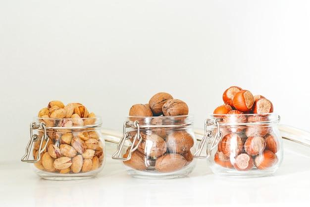 Selección variada de frutos secos: avellanas, pistachos y nueces en vidrio.