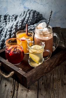 Selección de varias bebidas tradicionales de otoño: chocolate caliente con malvaviscos, té con limón y jengibre