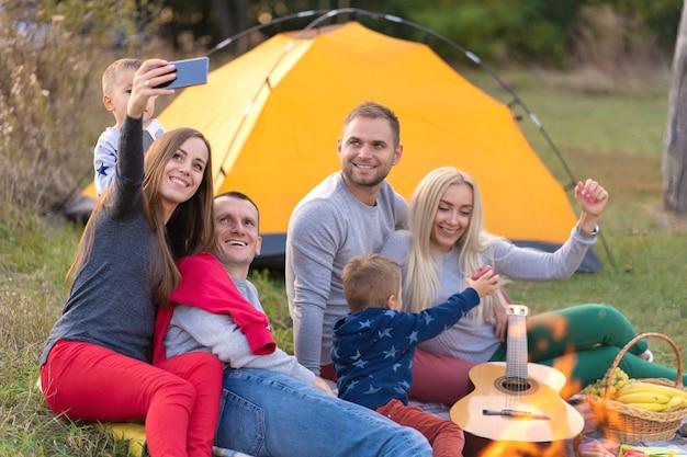 Selfie de amigos en la naturaleza. los amigos descansan cerca del lago. muy divertida compañía. gran familia reunida en vacaciones. niños y padres en un picnic en el bosque de verano.