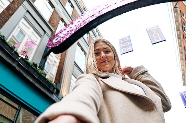 Selfie de ángulo bajo de una mujer rubia sonriente feliz en la calle.