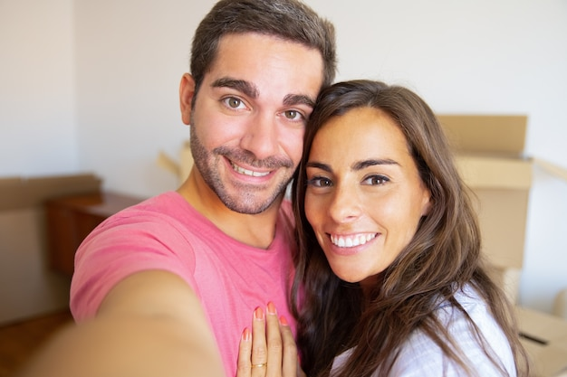 Selfie de la feliz pareja joven en su nuevo hogar, posando con cajas de cartón en el fondo, sosteniendo el gadget en la mano
