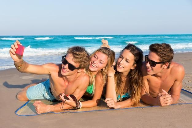 Selfie grupo de amigos turistas en una playa tropical.