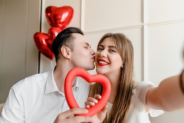Selfie de hombre y mujer enamorados de corazón y globos rojos en casa