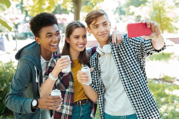 Selfie juntos. estudiantes modernos y radiantes que se sienten memorables mientras se hacen selfies juntos