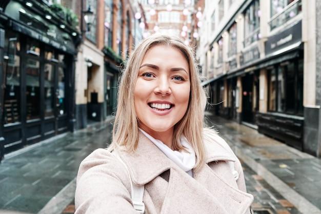 Selfie de una mujer rubia sonriente feliz en la calle. videollamada.