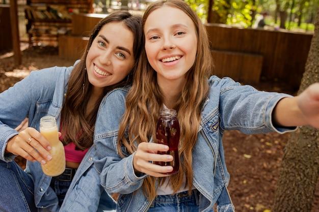 Selfie de mujeres jóvenes sosteniendo botellas de jugo fresco