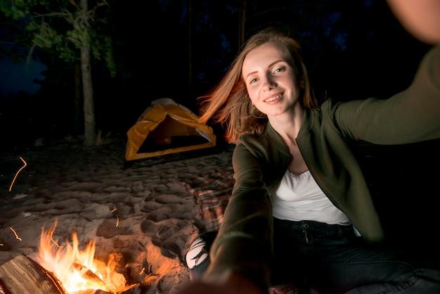 Selfie de niña acampando de noche por hoguera.