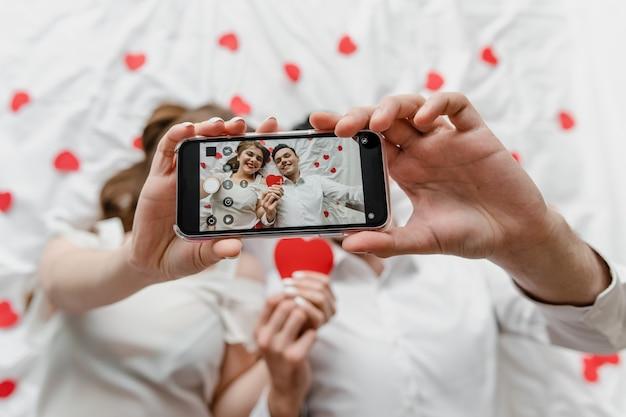 Selfie en la pantalla del teléfono del hombre y la mujer enamorados en la cama