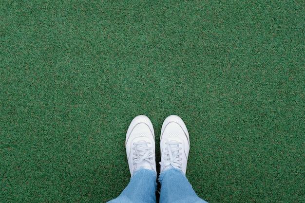 Selfie de pies en zapatillas de deporte blancas sobre fondo de hierba verde con espacio de copia, primavera y verano con concepto de estilo de vida de moda
