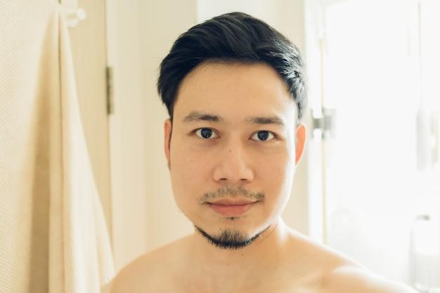Selfie retrato de hombre feliz en el baño.