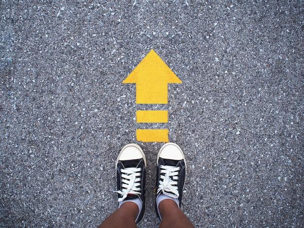 Selfie sneaker zapatos negros en camino de concreto con línea de flecha amarilla