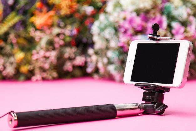 Selfie stick sobre fondo con flores