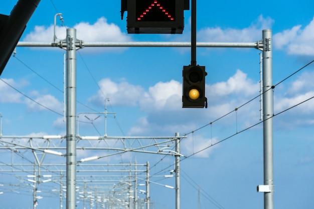 Semáforo de tráfico sobre las vías del ferrocarril o el día del cielo azul de la posada del metro.