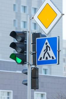 Semáforo verde, paso de peatones y señales de tráfico de la carretera principal