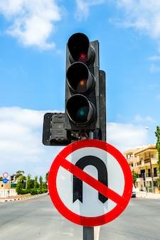 Semáforos y una señal que prohíbe un giro